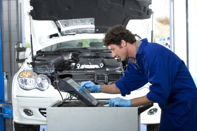 Auto repair man checking the diagnostics of this high end vehicle